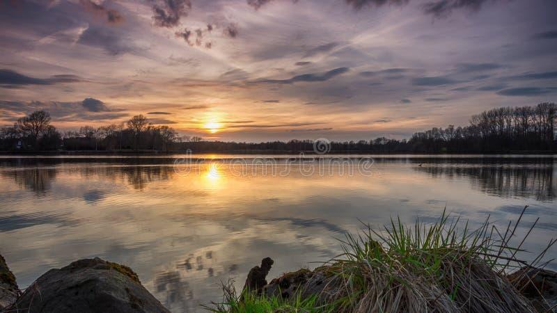 在湖的沈默日落的-石头和Gras在前景 库存图片