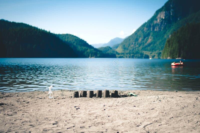 在湖的海滩的沙子城堡 图库摄影
