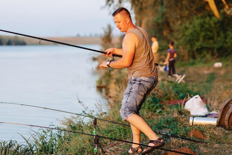 在湖的渔夫捉住的鲤鱼夏时的晚上 库存图片