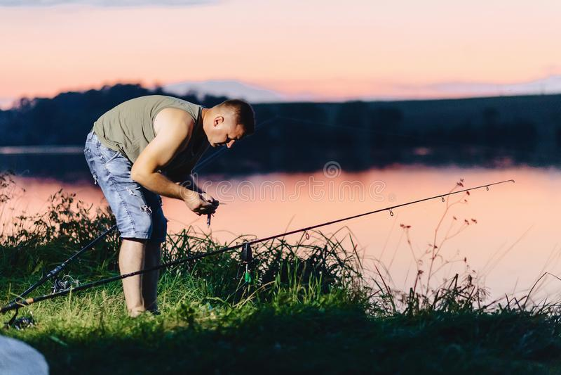 在湖的渔夫捉住的鲤鱼夏时的晚上 库存照片