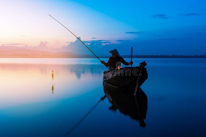 在湖的照片射击渔夫投掷的鱼网 Silhouett 库存照片