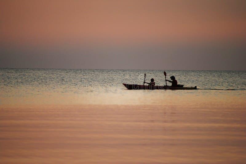 在湖的独木舟日落的 库存图片