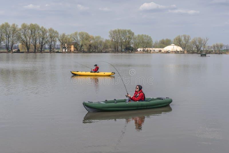 在湖的皮船钓鱼 inflateble小船的两位女渔翁与 免版税库存照片