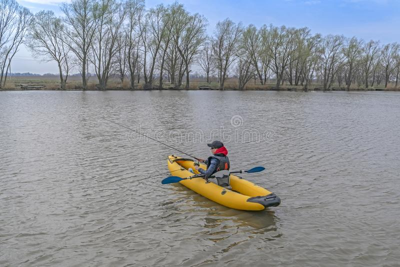 在湖的皮船钓鱼 inflateble小船的女渔翁有fishi的 库存照片