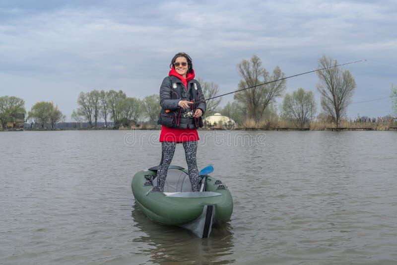 在湖的皮船钓鱼 inflateble小船的女渔翁有fishi的 免版税库存图片