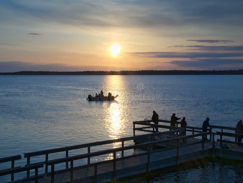 在湖的美好的日出有剪影的人钓鱼 库存图片