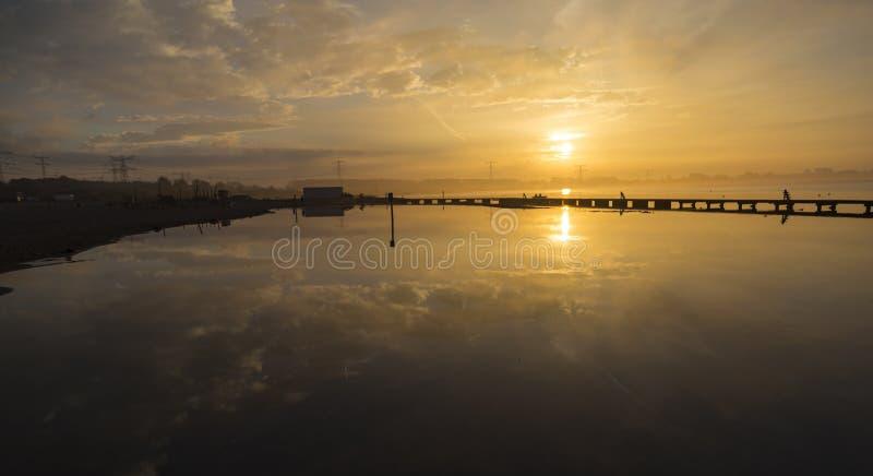 在湖的金黄日出 云彩的镜象反射在w的 库存照片