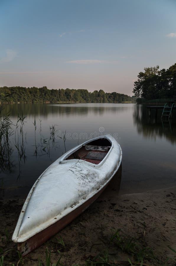 在湖的镇静水有一艘白色皮船的 免版税库存照片