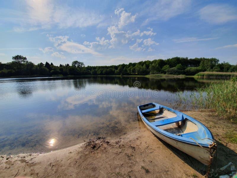 在湖边关闭的小船在summerday 免版税库存照片