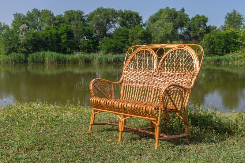 在湖边的柳条宽椅子 免版税库存图片