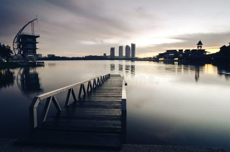 在湖边的美好的早晨 在湖表面,软和剧烈的云彩的大厦反射与五颜六色在天空 免版税库存图片