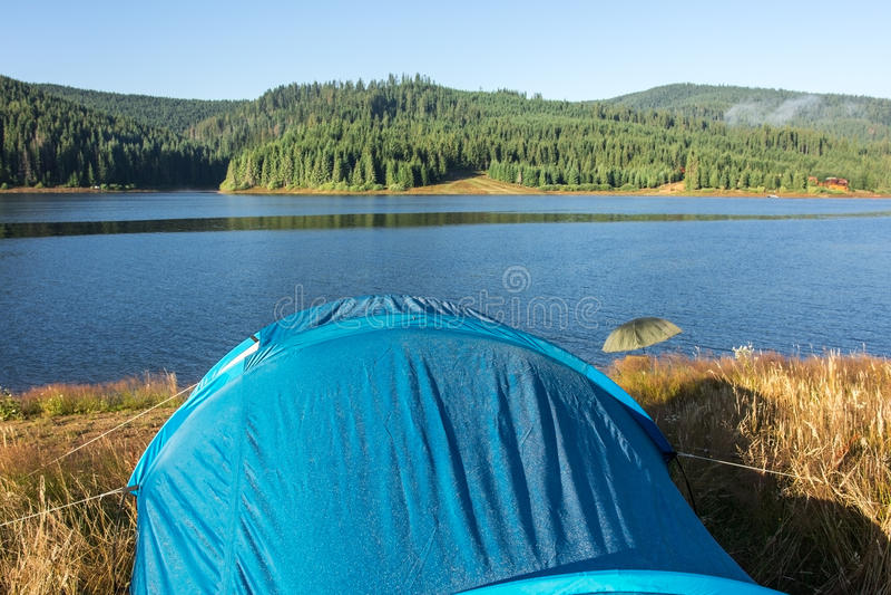 在湖边的蓝色帐篷,清早 免版税库存照片
