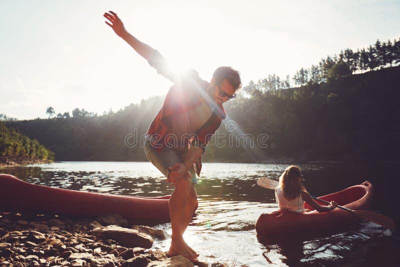 在湖边缘的年轻人有妇女乘独木舟的 免版税图库摄影