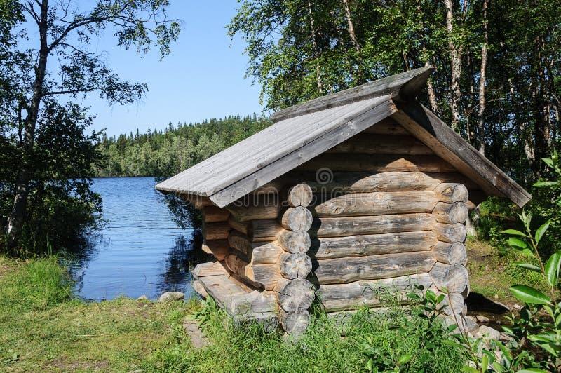 在湖银行的小木客舱 图库摄影