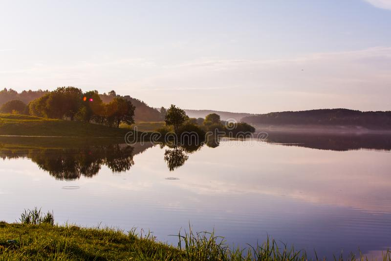 在湖附近的平安的晚上在夏天 结构树和天空 库存图片