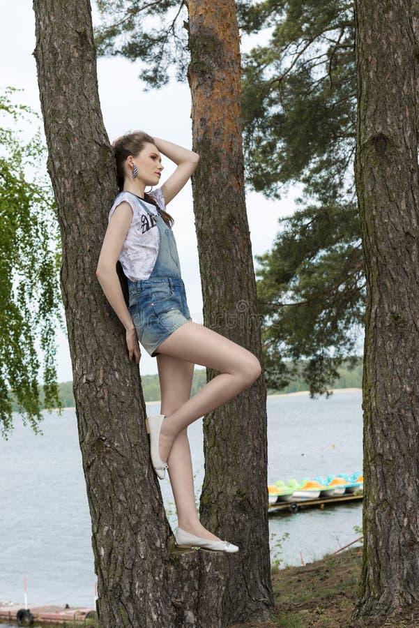 在湖附近的时髦都市女孩 免版税库存图片
