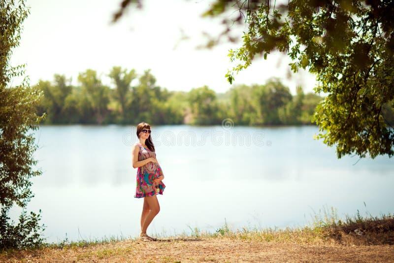 在湖附近的怀孕的女孩 库存照片