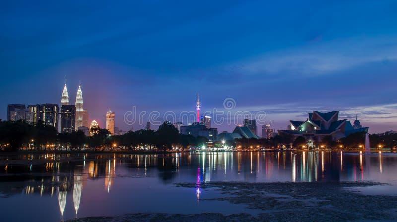 在湖附近的美好的日落打开了与吉隆坡市光 免版税库存图片