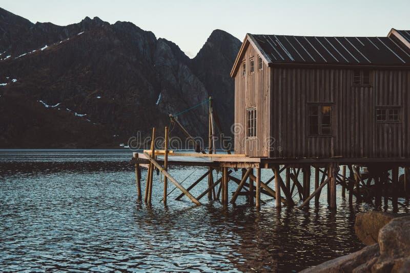 在湖附近的老木钓鱼的房子以山为背景 挪威,欧洲 r 能使用  库存照片