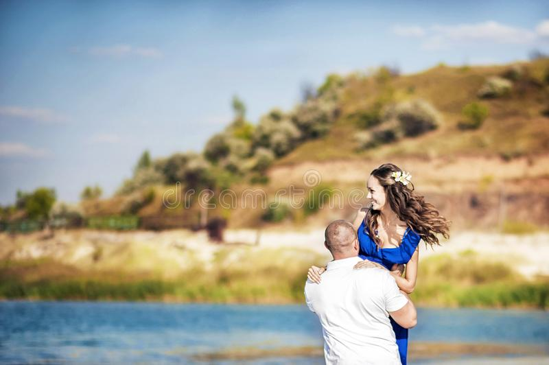 在湖,沿水跑的海的岸的一对爱恋的夫妇 在爱在海的夏天奔跑与飞溅水 爱 免版税库存图片