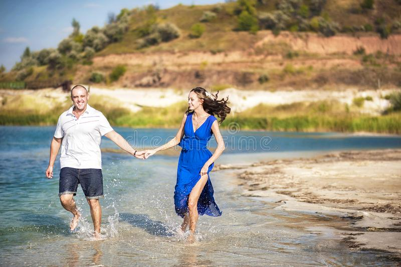 在湖,沿水跑的海的岸的一对爱恋的夫妇 在爱在海的夏天奔跑与飞溅水 爱 免版税图库摄影