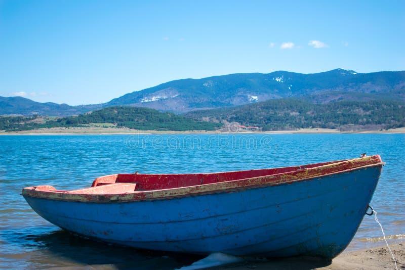 在湖Batak的小船有在距离的山的 库存图片