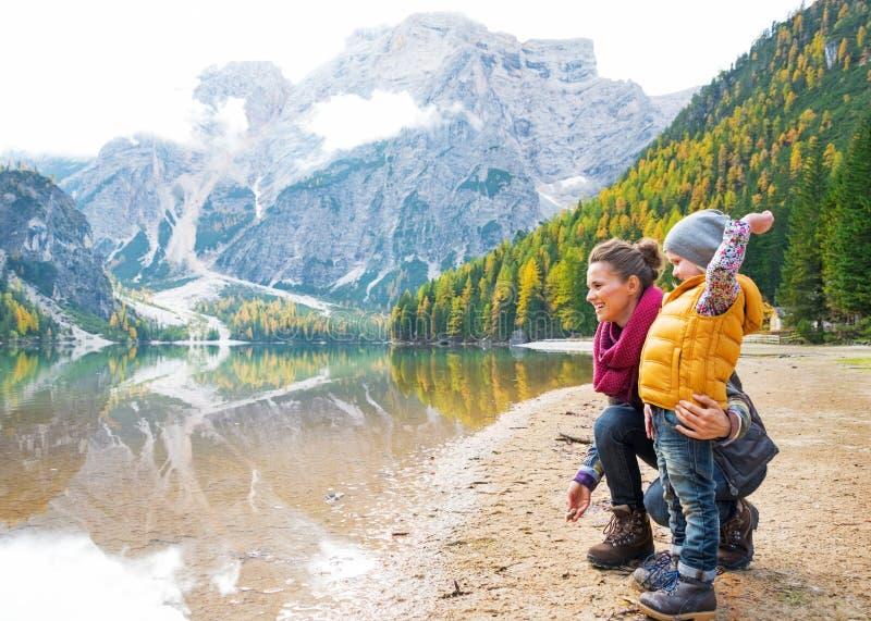 在湖braies的母亲和婴孩投掷的石头 库存照片
