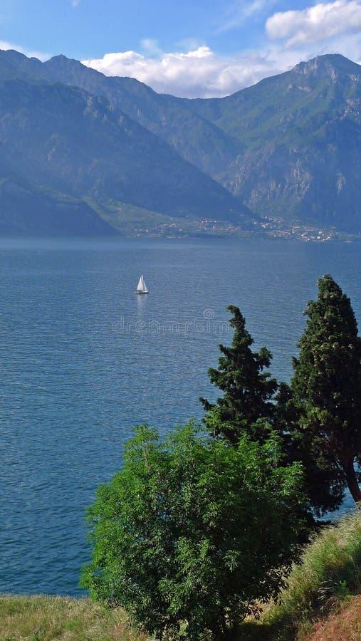 在湖garda :山、树、水和帆船 免版税库存图片