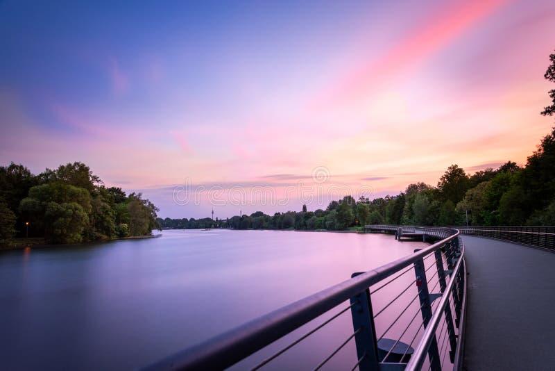 在湖Woehrder的桃红色云彩在纽伦堡看见和一座桥梁 免版税库存照片