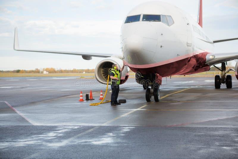 在湿机场跑道的工作者充电的飞机 库存图片
