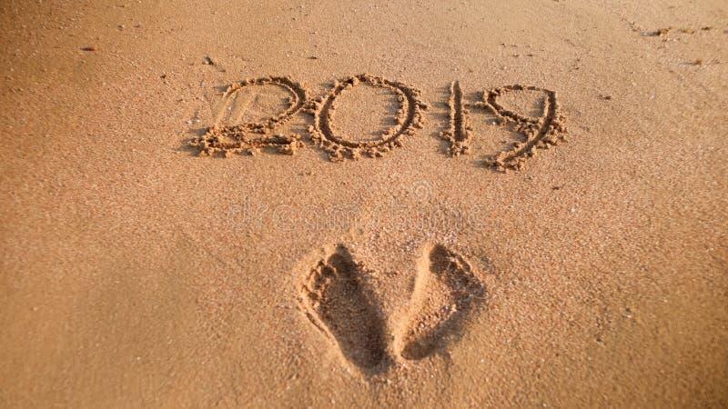 在湿沙子和2019个数字的写的特写镜头图象脚印在海海滩 新年,圣诞节的概念和 免版税库存图片