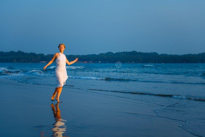 在湿沙子的快乐的年轻女人跳舞,做姿态在海湾温暖的夏天晚上的背景 无忧无虑的假日 免版税库存照片