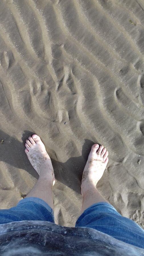 在湿沙子的男孩的脚在海滩 免版税库存图片