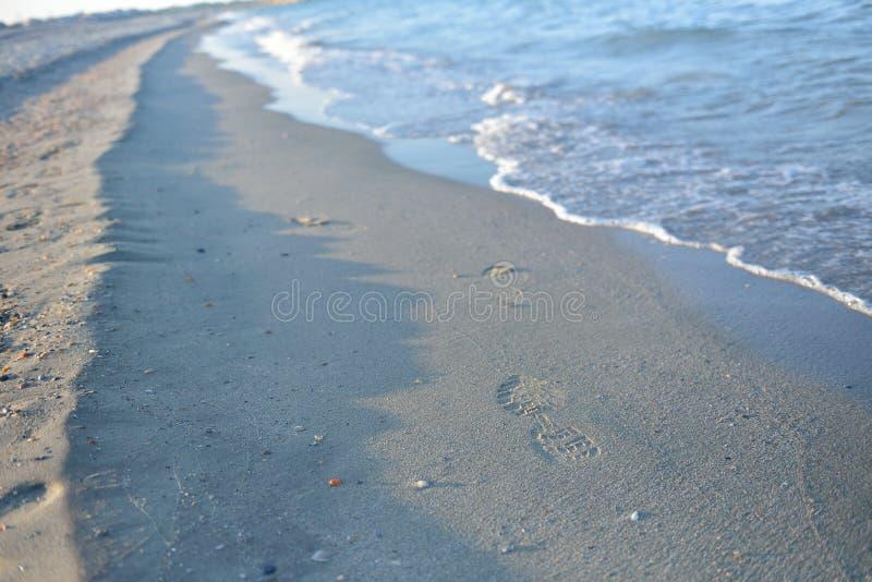 Download 在湿沙子的脚印,在日落的波浪在一个安静的海滩 钛 库存图片. 图片 包括有 横向, 休闲, 背包, 版本记录 - 72369707