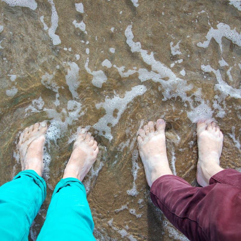 在湿沙子的脚在海滩 免版税库存图片