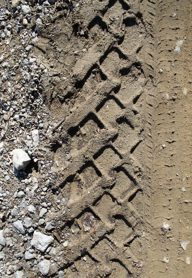 在湿泥泞的足迹皇族,路,抽象背景,纹理材料的车胎轨道 在土沙子或泥的轮胎轨道,减速火箭 免版税库存图片