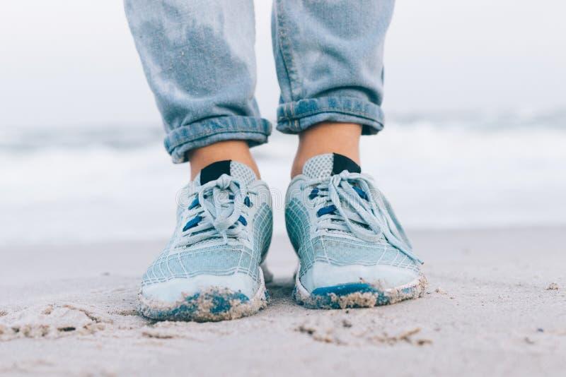 在湿牛仔裤和运动鞋的女性脚 免版税库存照片