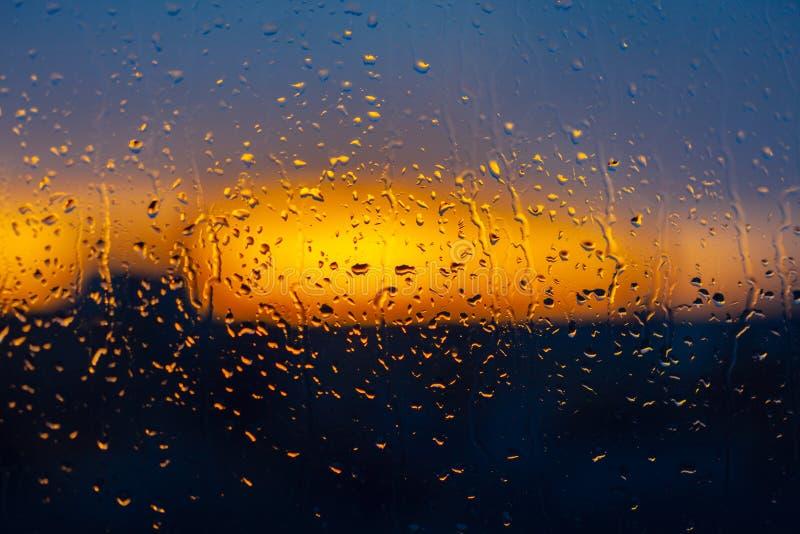 在湿窗口后的被弄脏的日落背景 免版税库存图片