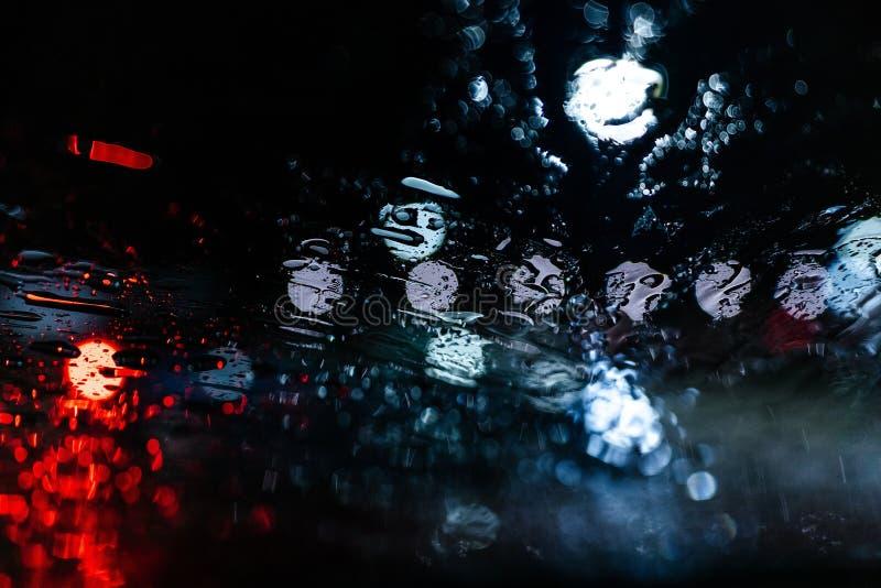 在湿窗口的被弄脏的汽车光 图库摄影