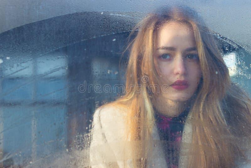 在湿玻璃后的哀伤的美丽的seksalnaya相当哀伤的孤独的女孩与在外套的大哀伤的眼睛 图库摄影