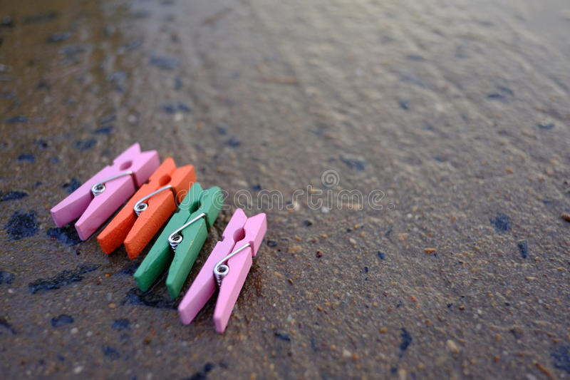 在湿roadcement背景的五颜六色的晒衣夹 库存照片
