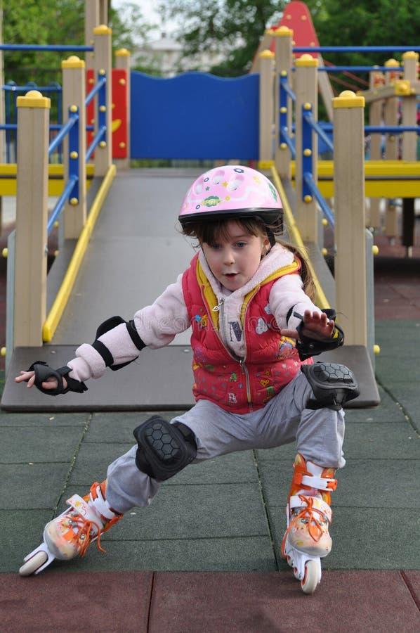 在溜冰鞋的女孩骑马 免版税图库摄影