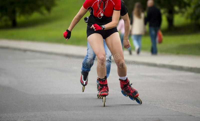 在溜冰鞋的妇女骑马在室外冰鞋公园 免版税库存图片