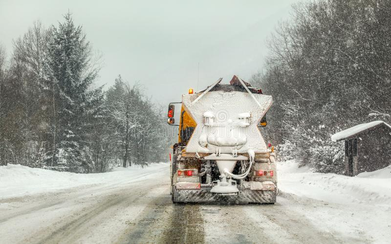 在溜滑路,重下雪和树的积雪的橙色高速公路维护铺砂机卡车在背景中 免版税库存照片