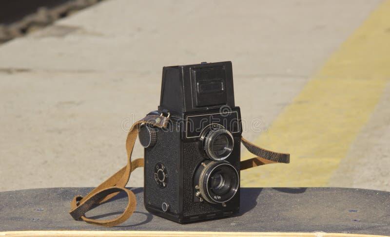 在滑板的葡萄酒照相机 库存照片