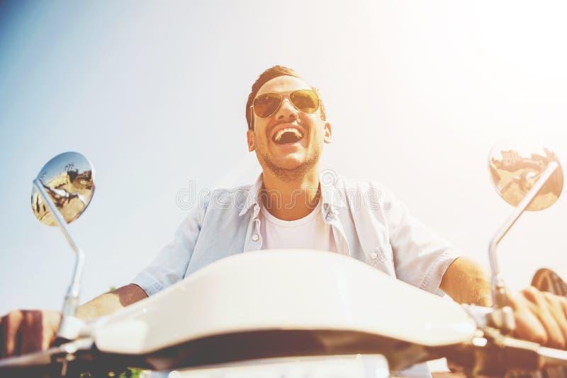 在滑行车的微笑的年轻人骑马沿街道 免版税库存照片