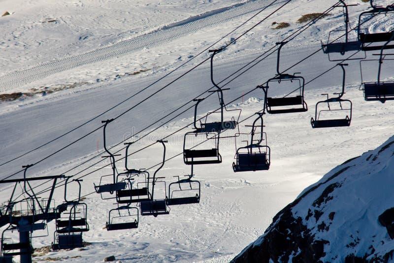 在滑雪倾斜上的空的滑雪电缆车 库存图片