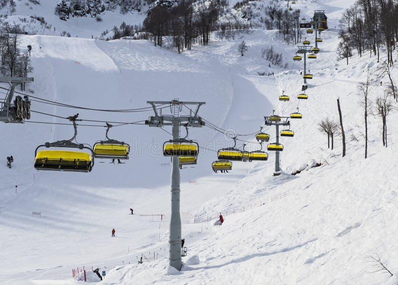 在滑雪倾斜背景的驾空滑车在罗莎Khutor 免版税库存图片