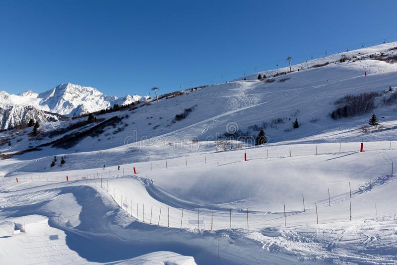 在滑雪场的倾斜在阿尔卑斯,法国 晴朗的冬日 背景海滩异乎寻常的做的海洋沙子雪人热带假期白色冬天 免版税库存图片
