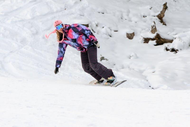 在滑雪道的妇女雪板运动在冬天 免版税库存照片